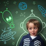 Imagination and dreams of a child, dressed as a space man in front of a blackboard with chalk drawings of space rocket and alien, concept for aspirations and daydreaming